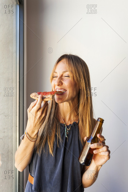 Woman holding beer and taking bite of pizza