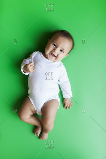 Smiling baby girl on a green background