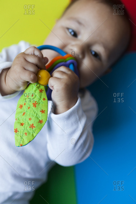 Baby on a colorful background playing with toys
