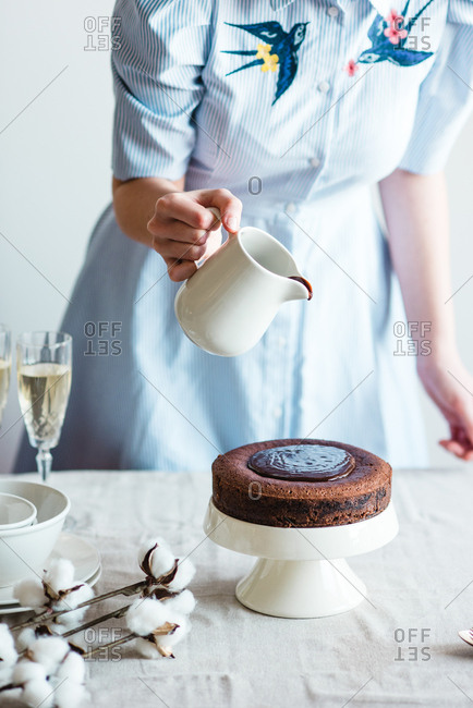 Woman icing a chocolate cake