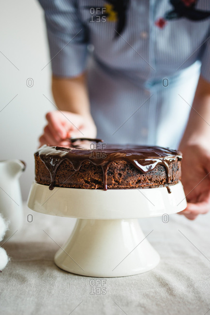 Woman spreading icing on chocolate cake