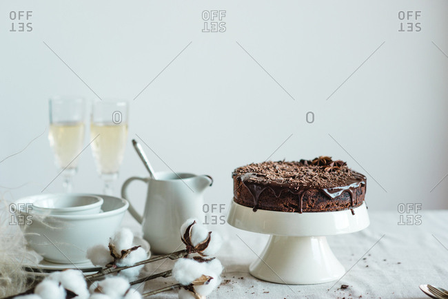 Chocolate cake with icing and sprinkles served on cake stand