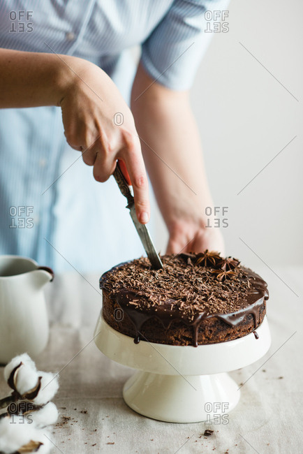 Person slicing a homemade chocolate cake on a cake stand