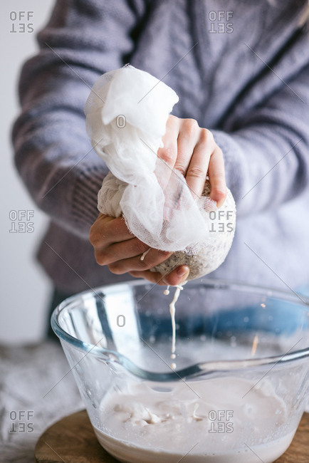Person preparing homemade almond milk