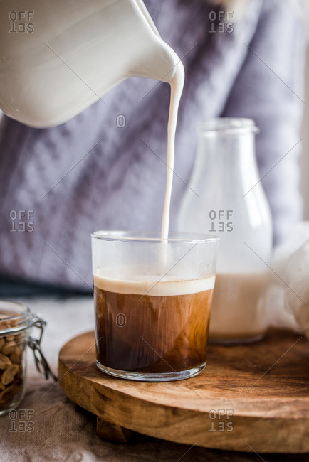 Person pouring cream into a coffee cup