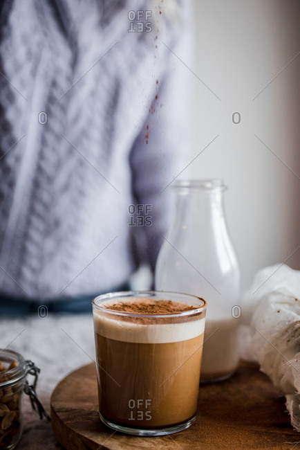 Person sprinkling topping onto coffee