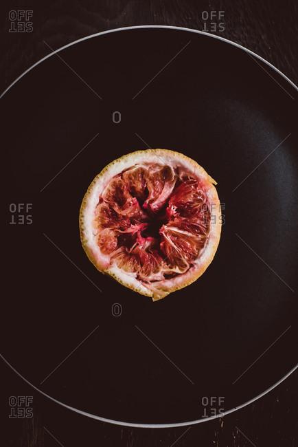 Blood orange on black dish