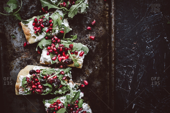 Ricotta flatbread with pomegranate salsa on a baking tray
