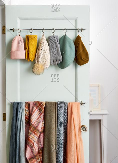 Winter accessories organized on a door