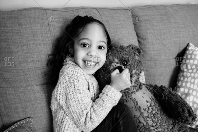 Excited little girl sitting on couch with worn teddy bear
