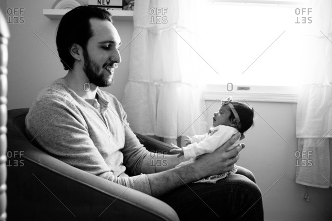 Happy father holding baby in living room chair