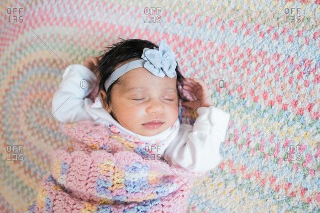 Sweet newborn sleeping peacefully in pastel blanket