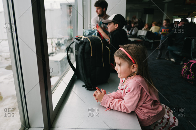 Girl looking out airport window waiting for flight