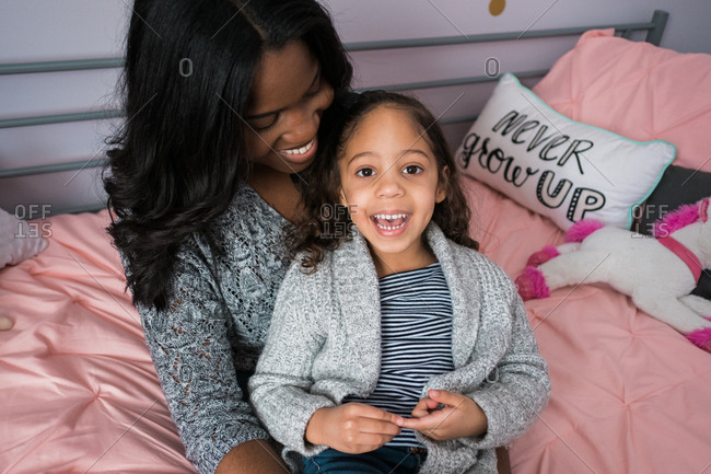 Daughter sitting in smiling mother's lap in her bedroom