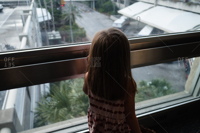Little girl looking out window from upper level to outside