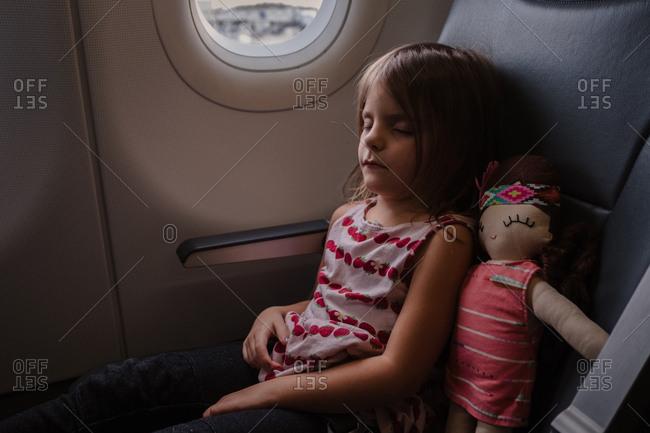 Young girl sleeping on plane with stuffed doll