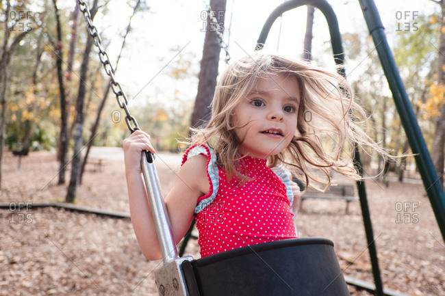 Sweet little girl swinging on playground