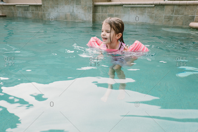 Happy girl swimming in outdoor pool with floatation devices