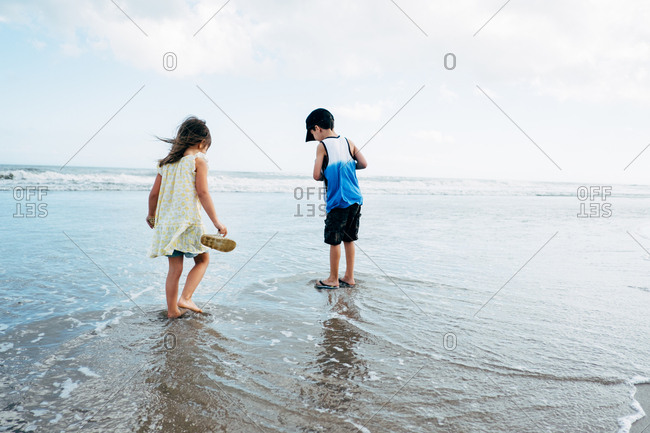 Kids exploring beach together barefoot