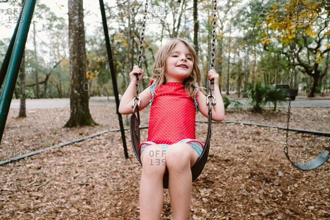 Happy girl sitting on swing set in fall