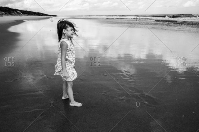 Young girl barefoot on wet beach enjoying view of ocean