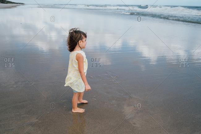 Small child on shore watching ocean waves splashing