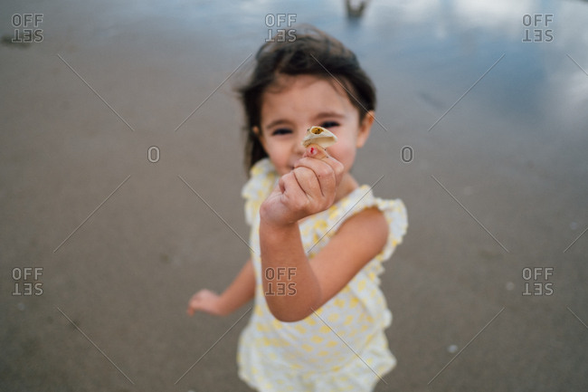 Small girl showing off shell on beach