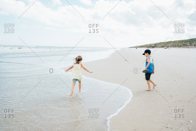 Barefoot siblings playing on beach together