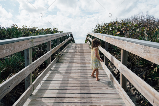 Young girl standing on wooden beach dock alone