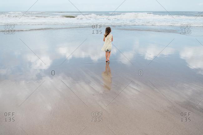 Little girl on beach watching waves splashing
