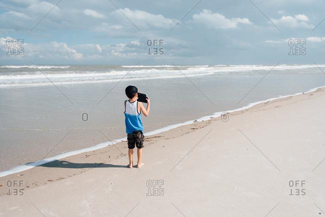 Boy taking photos on the sandy beach