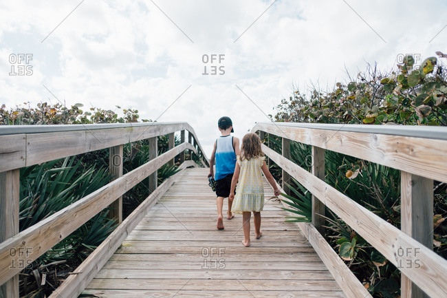 Brother and sister walking along wooden dock towards beach
