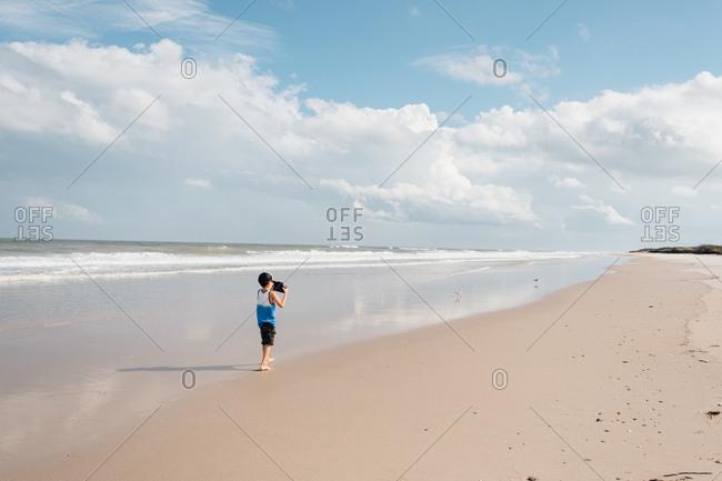 Little boy capturing scenic snapshots of beach on summer vacation