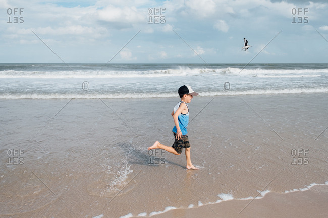 Boy with cap chasing seagulls on beach