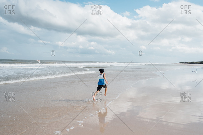 Young boy with ball cap running through water on coast