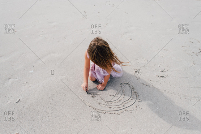 Creative little girl drawing in sand at the beach