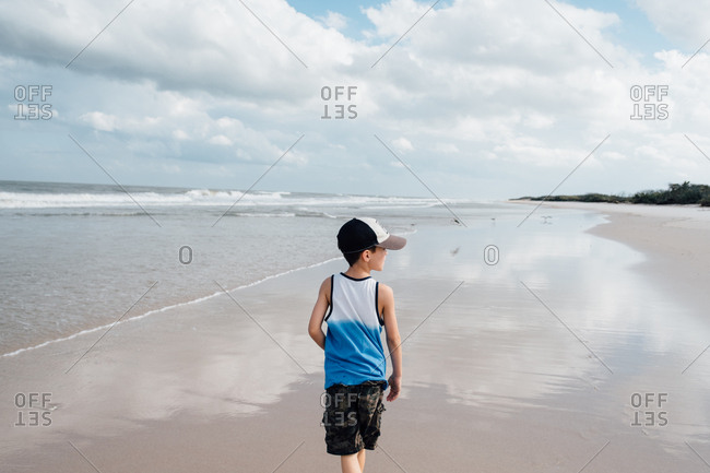 Little boy standing on wet beach enjoying view of birds and ocean