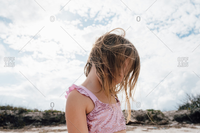 Girl standing in breeze on beach with eyes closed