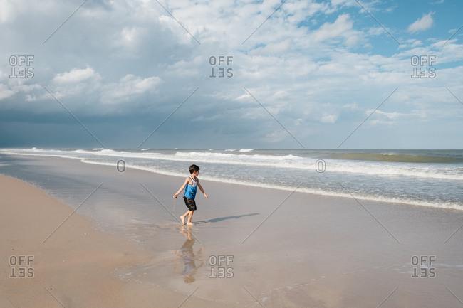 Boy flinging handful of sand into ocean