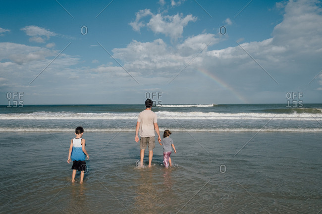 Father and kids enjoying view of rainbow wading in shallow water at the beach