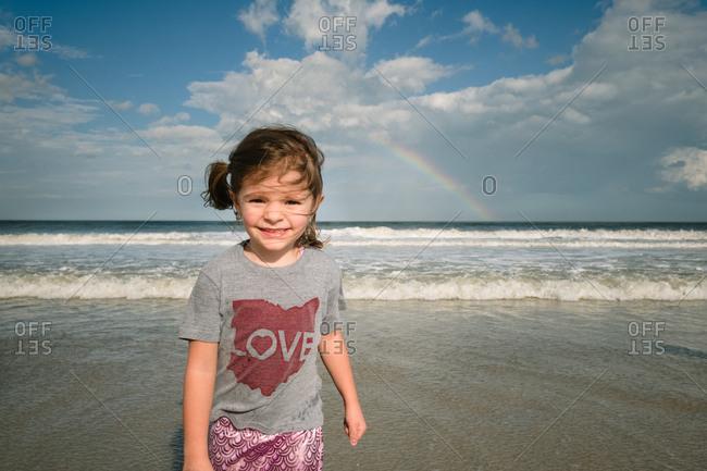 Happy girl standing in front of ocean rainbow