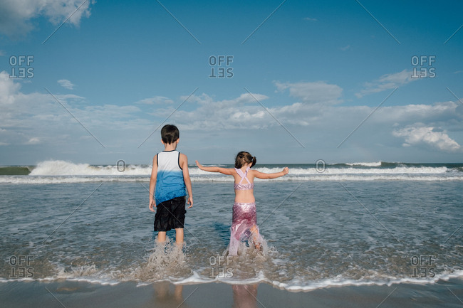 Siblings standing in low tide with water splashing at feet