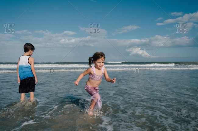 Sister running away from brother in water at the beach