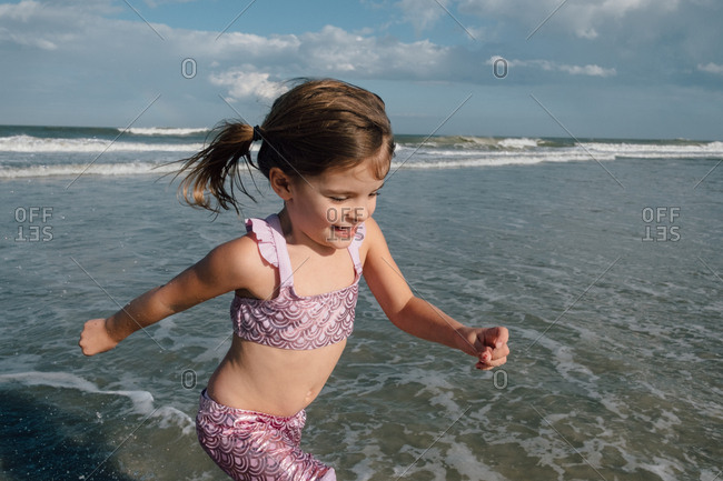 Happy little girl running through ocean water on summer vacation