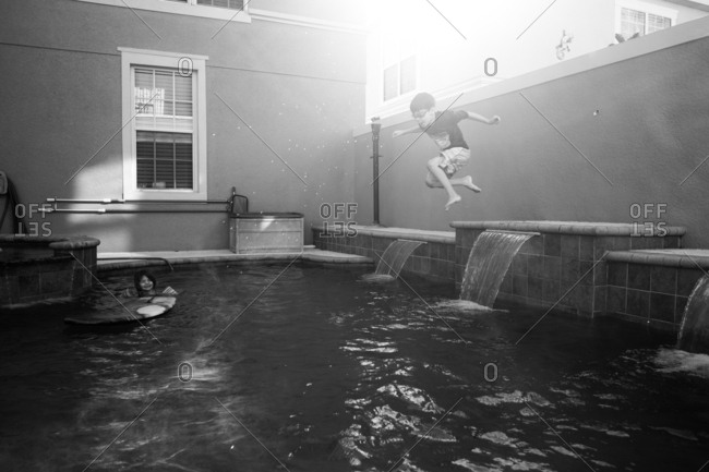 Monochrome action shot of boy jumping off pool ledge into water