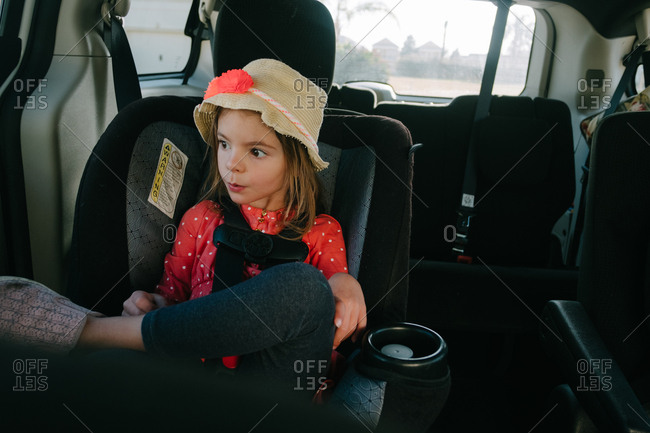 Little girl waiting in car seat alone looking out window