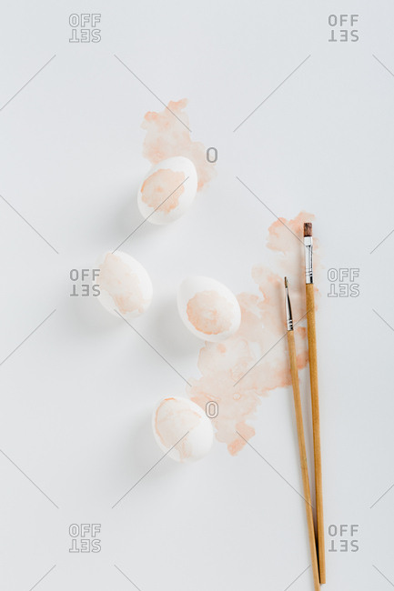 Overhead studio shot of four watercolored eggs with paintbrushes