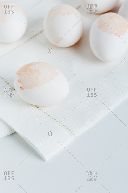 Close-up of watercolor stained egg on light folded napkin