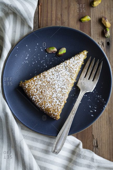 Cake slice on blue plate with powdered sugar