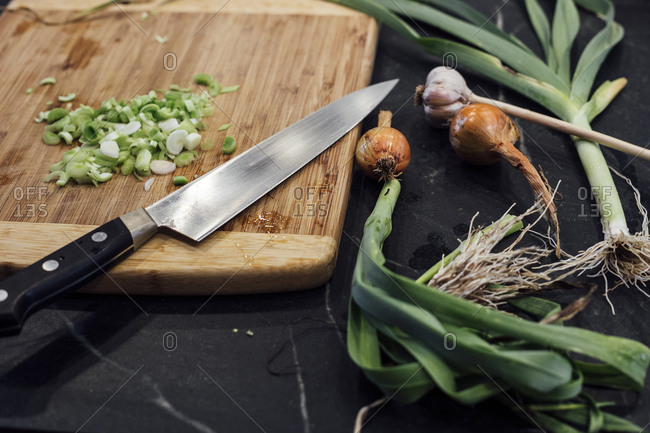 Close up of leek, shallot, and garlic being chopped on wooden cutting board